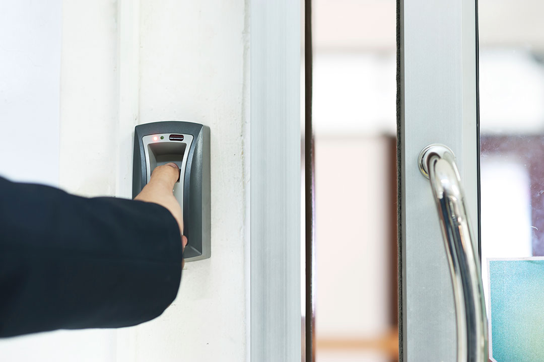 Employee using his thumb print to enter the office